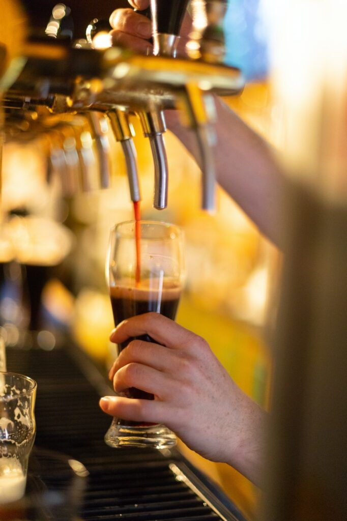 Dark beer is poured into a glass of beer tap